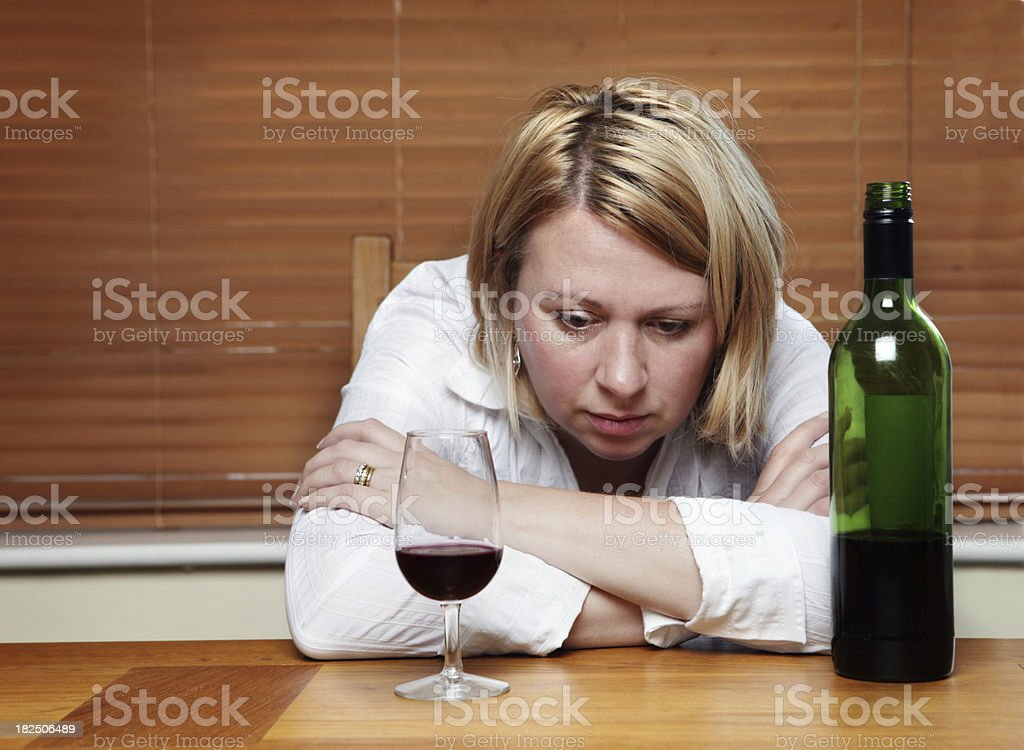A depressed woman in front of a wine cup and wine bottle stock photo