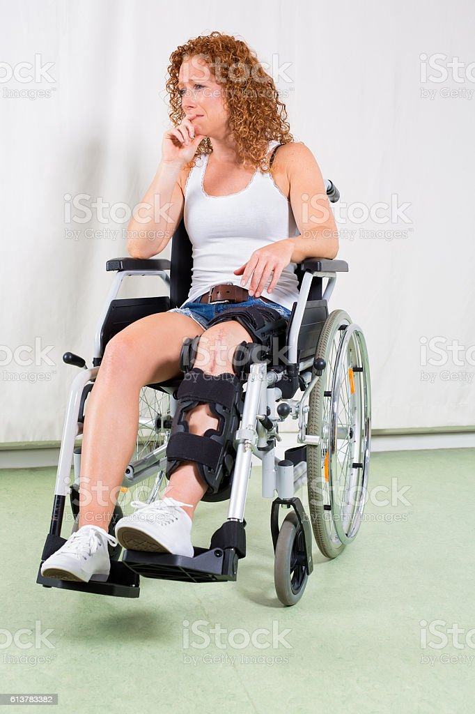 Depressed woman in wheelchair with hand to lip. stock photo