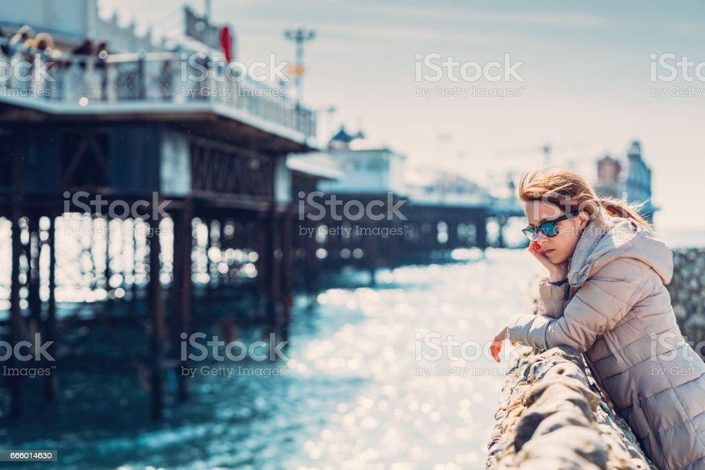 Depressed woman looking the ocean in Brighton city stock photo