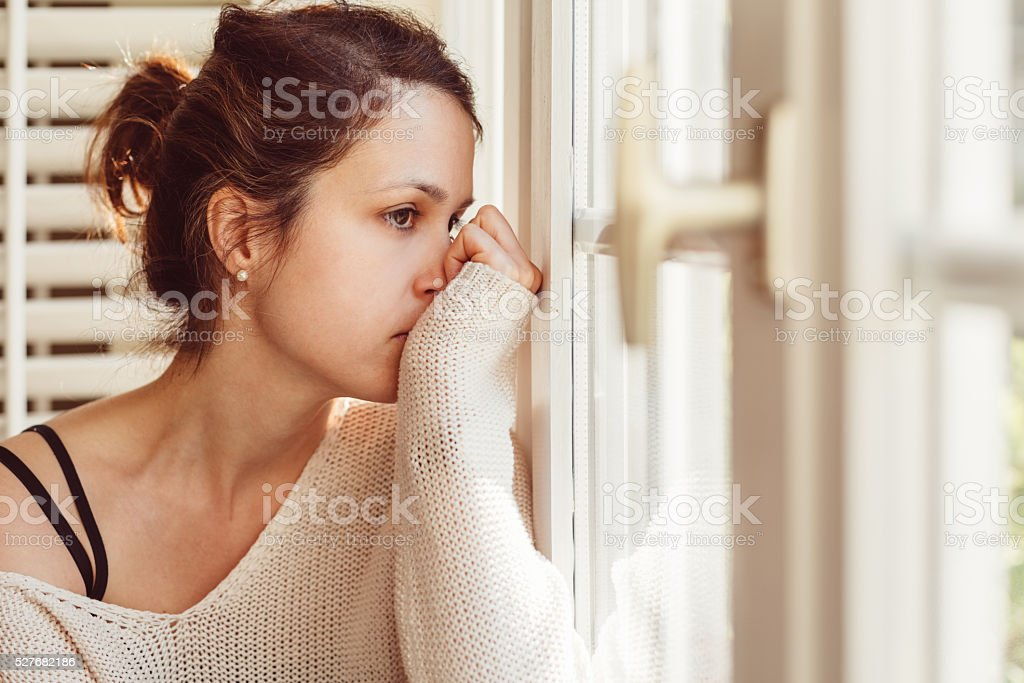Depressed woman looking through window stock photo