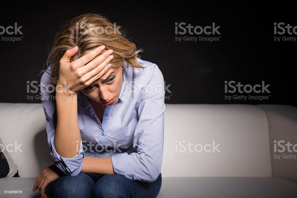 Depressed woman pressing her hand against her forehead stock photo