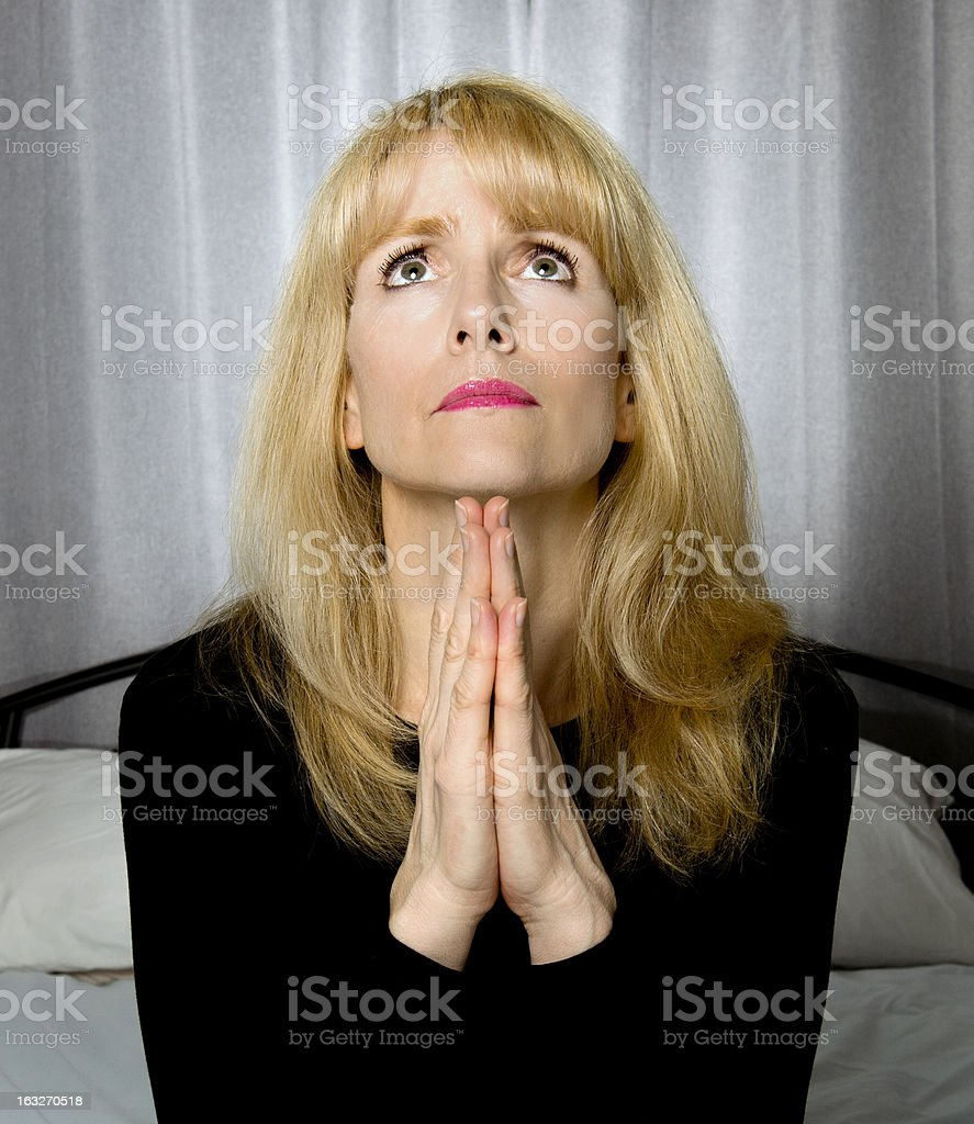 Depressed woman sits on bed praying royalty-free stock photo