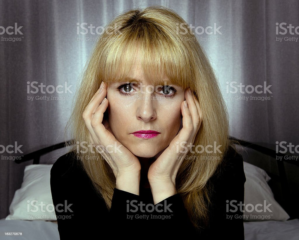 Depressed woman sits on bed with hands to face royalty-free stock photo