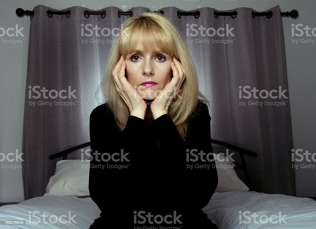 Depressed woman sits on bed with hands to head royalty-free stock photo