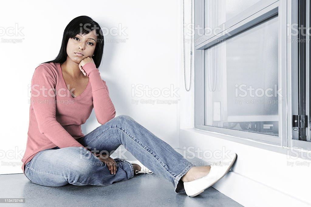 Depressed woman sitting on floor stock photo