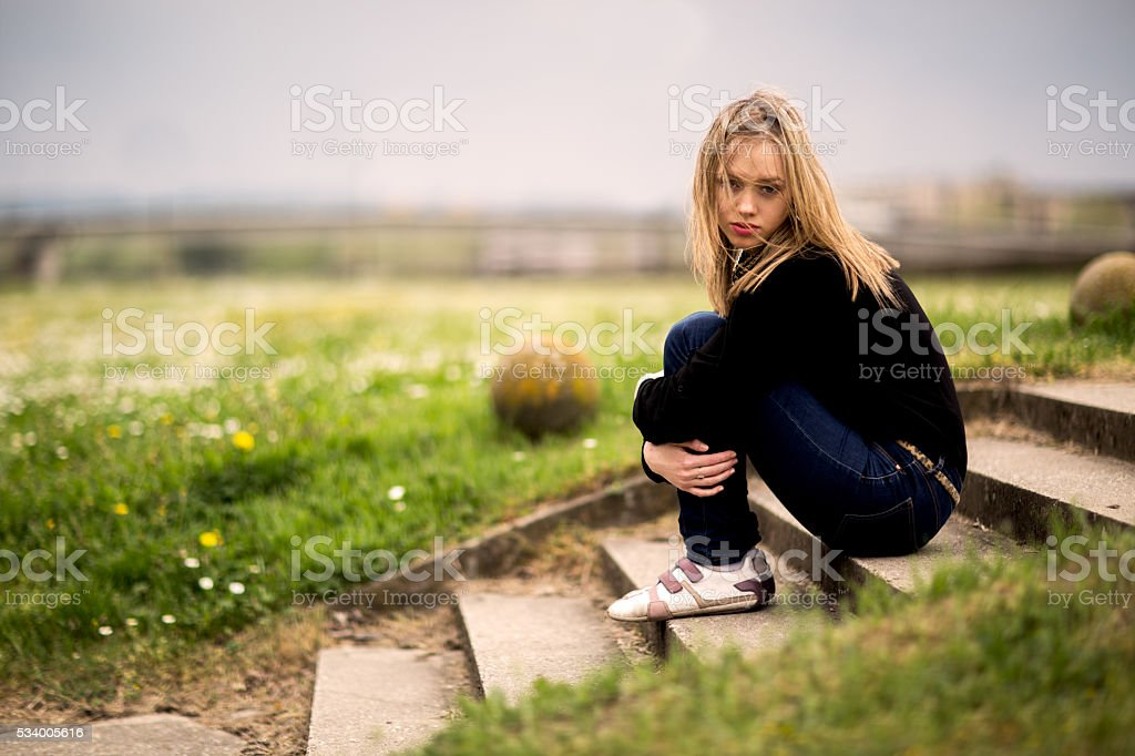 Depressed woman sitting on staircase in nature. stock photo