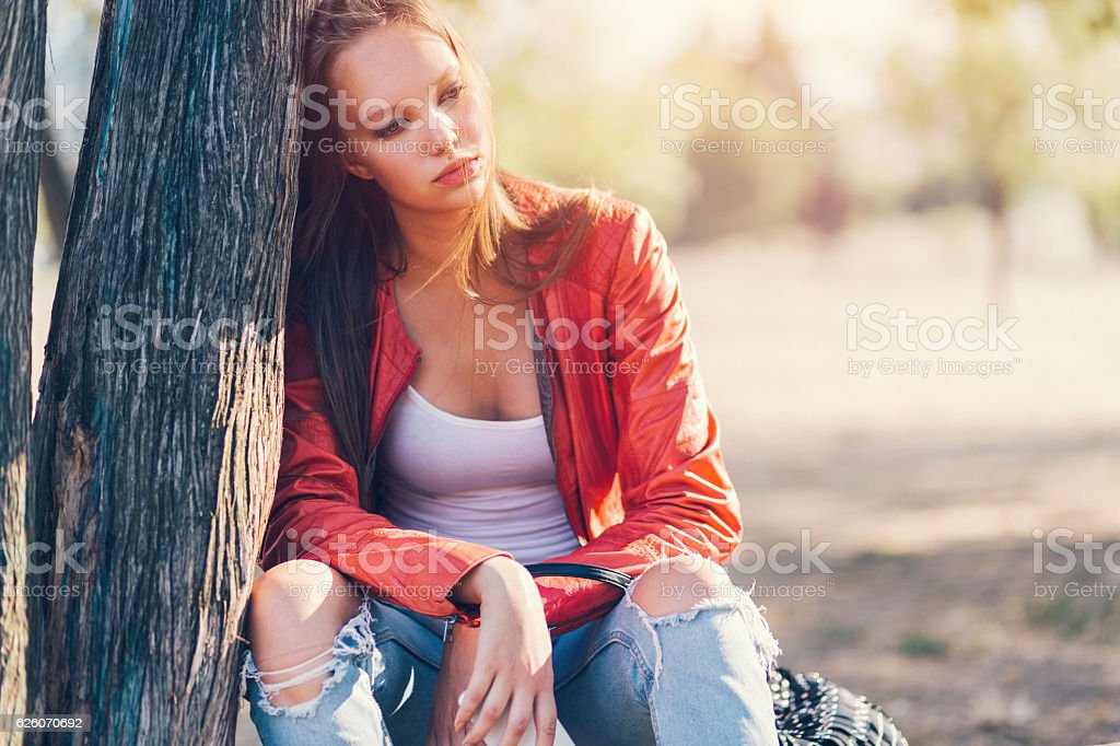 Depressed woman sitting outside stock photo