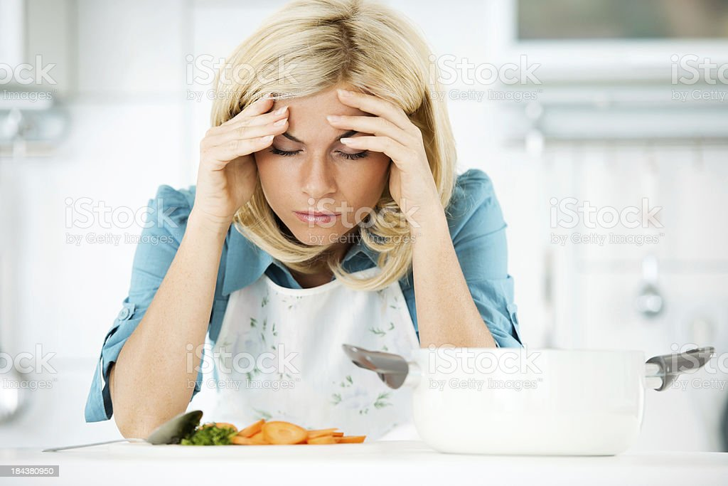Depressed woman tired of preparing meals. stock photo