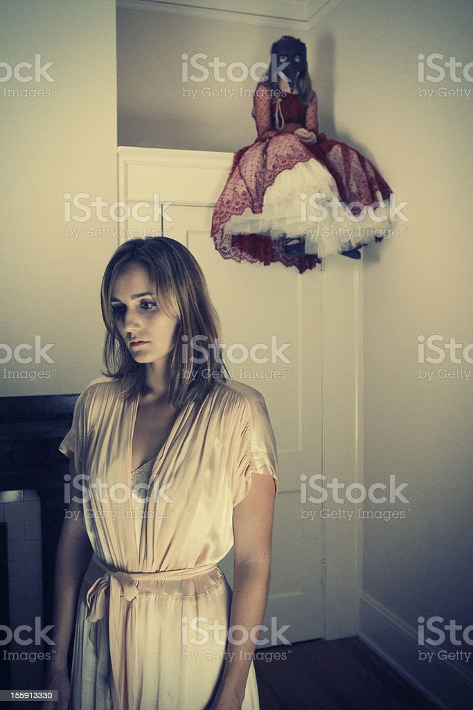 Depressed Woman with creepy little girl sitting above door royalty-free stock photo