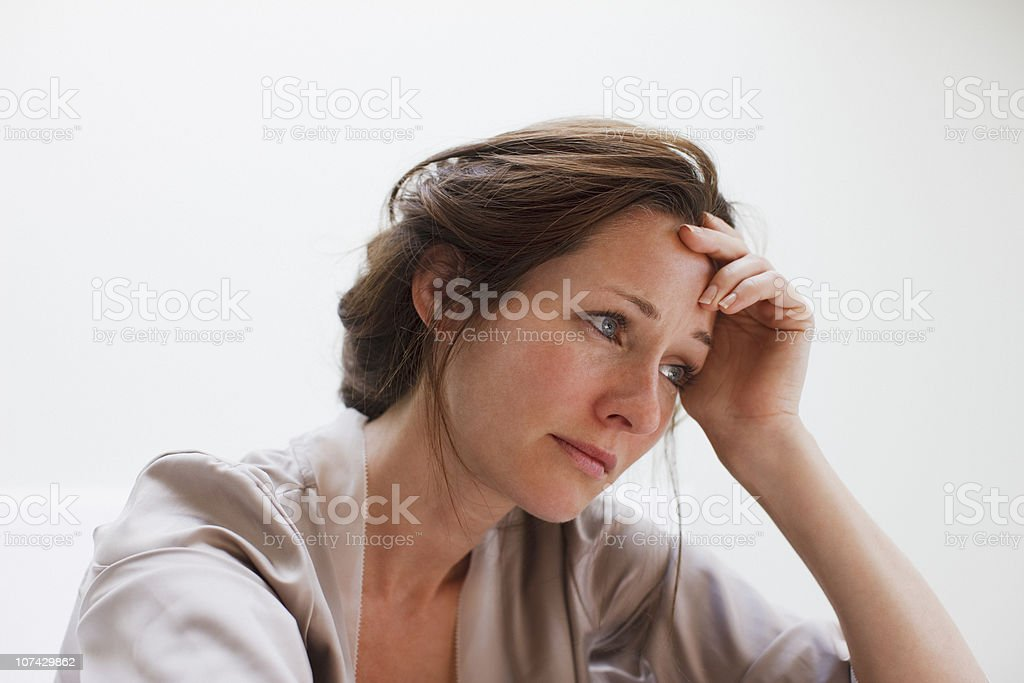 Depressed woman with head in hands stock photo