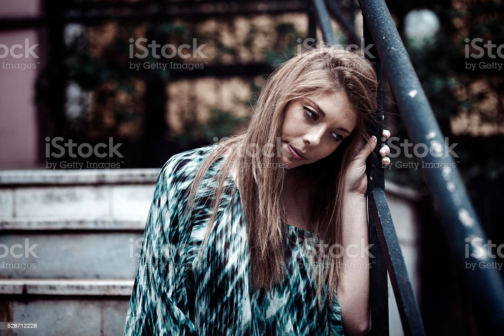 Depressed young adult sitting lonely outdoors stock photo