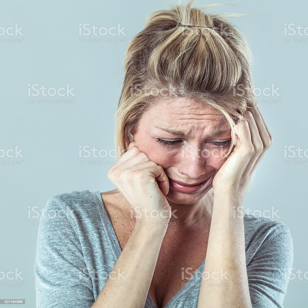 drama concept - depressed young blond woman in pain with big tears...