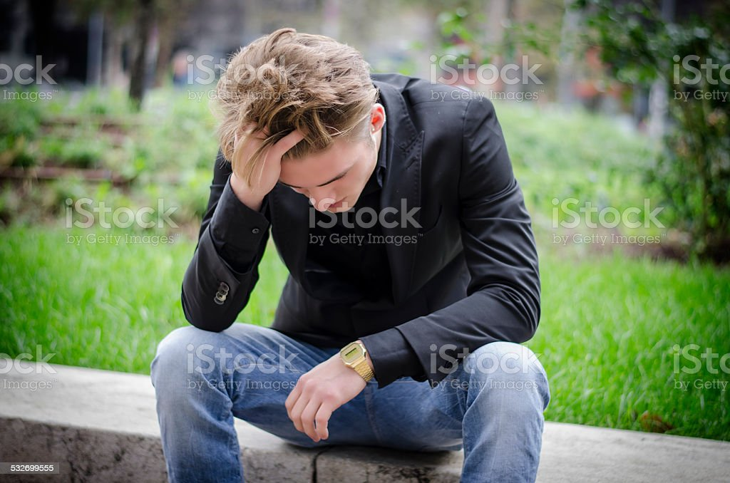 Depressed Young White Man Sitting at Street Side stock photo