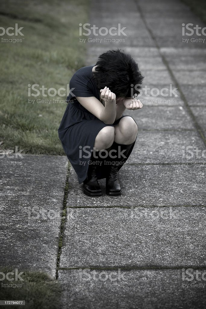Depressed Young Woman Crouching on Sidewalk, Head in Hands, Copyspace royalty-free stock photo