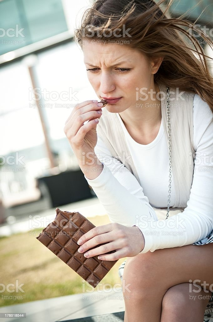 Depressed young woman eating chocolate royalty-free stock photo