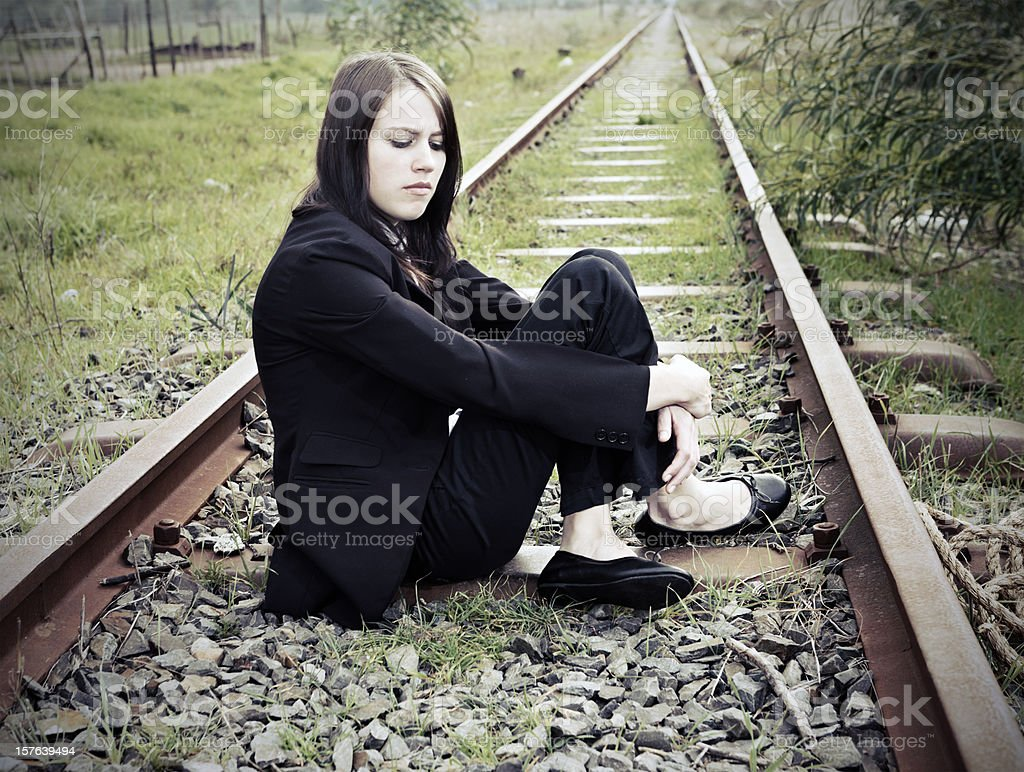 Depressed young woman sits on railway tracks stock photo