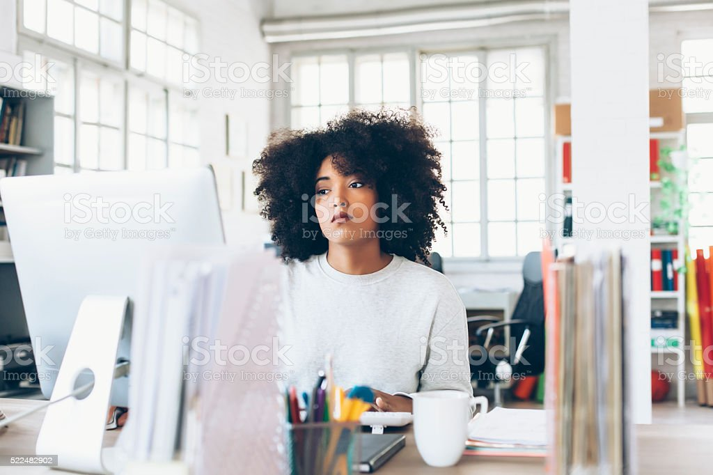 Depressed young woman using computer at the office stock photo
