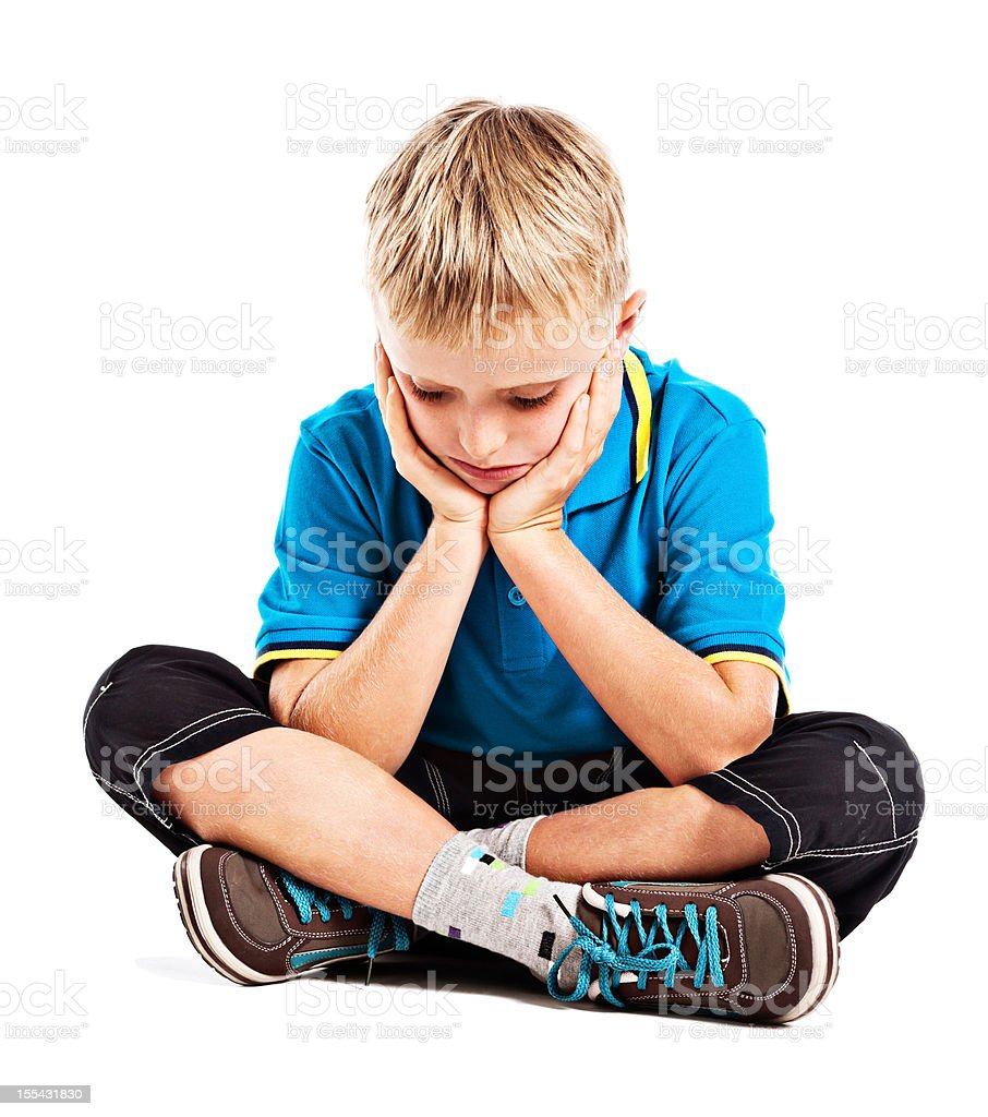 Depressed-looking little boy sits looking down head in hands stock photo