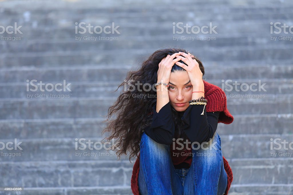 Depression and sadness in one woman on the stairs stock photo