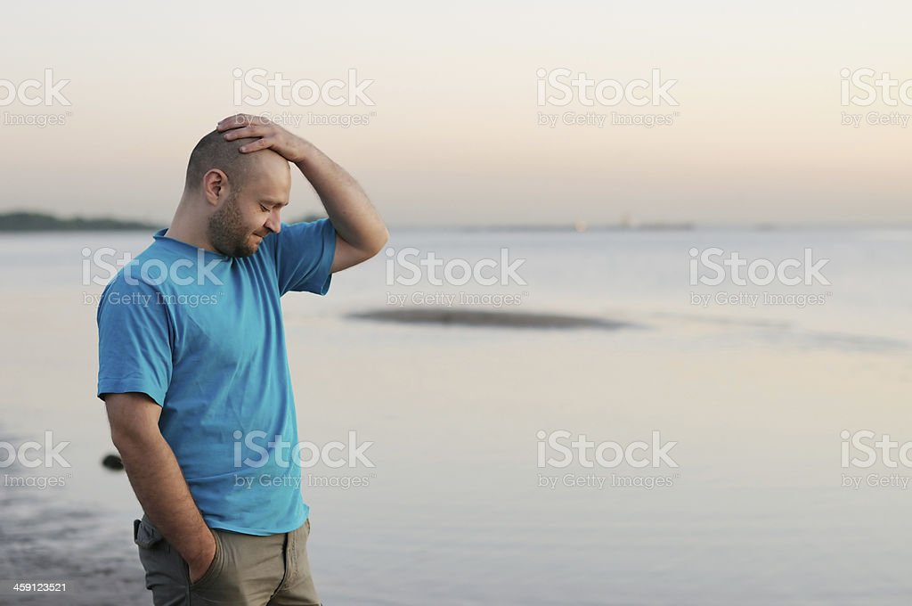 Depression - Bald man standing by the sea stock photo
