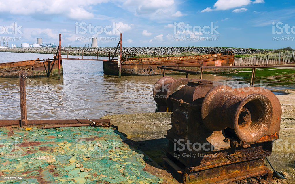 Derelict machinery and river boats in the Humber estuary, UK. stock photo