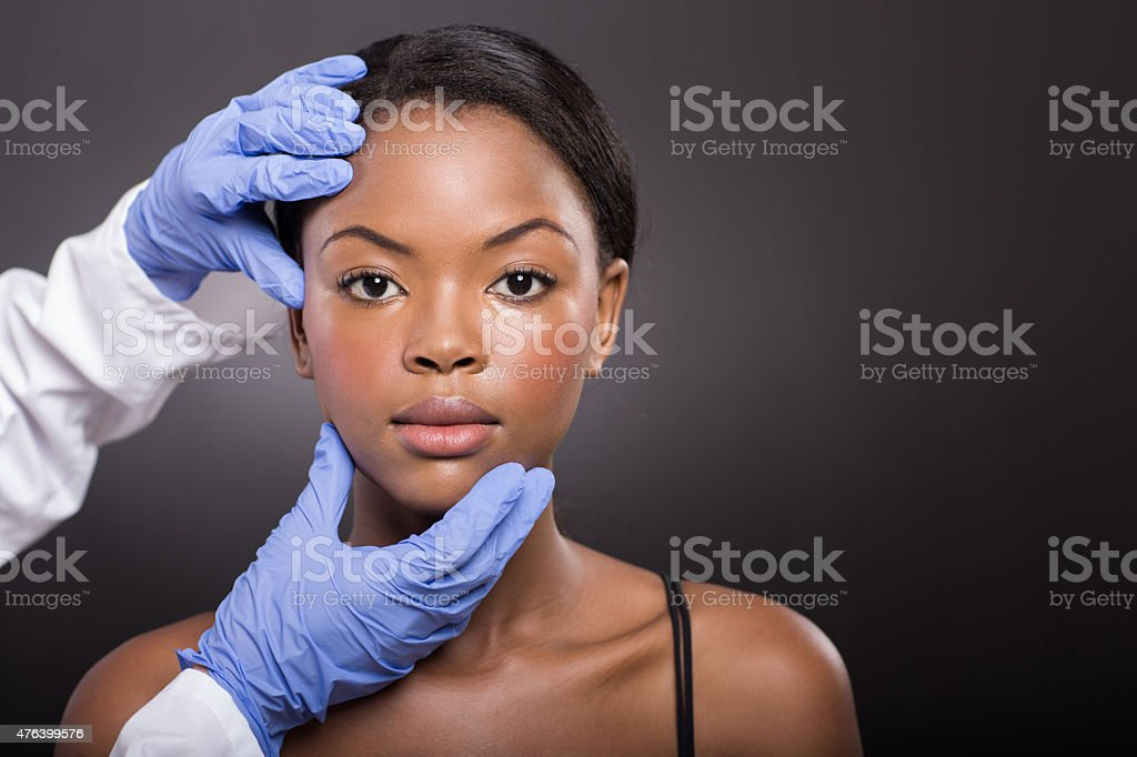 dermatologist checking african woman face skin stock photo
