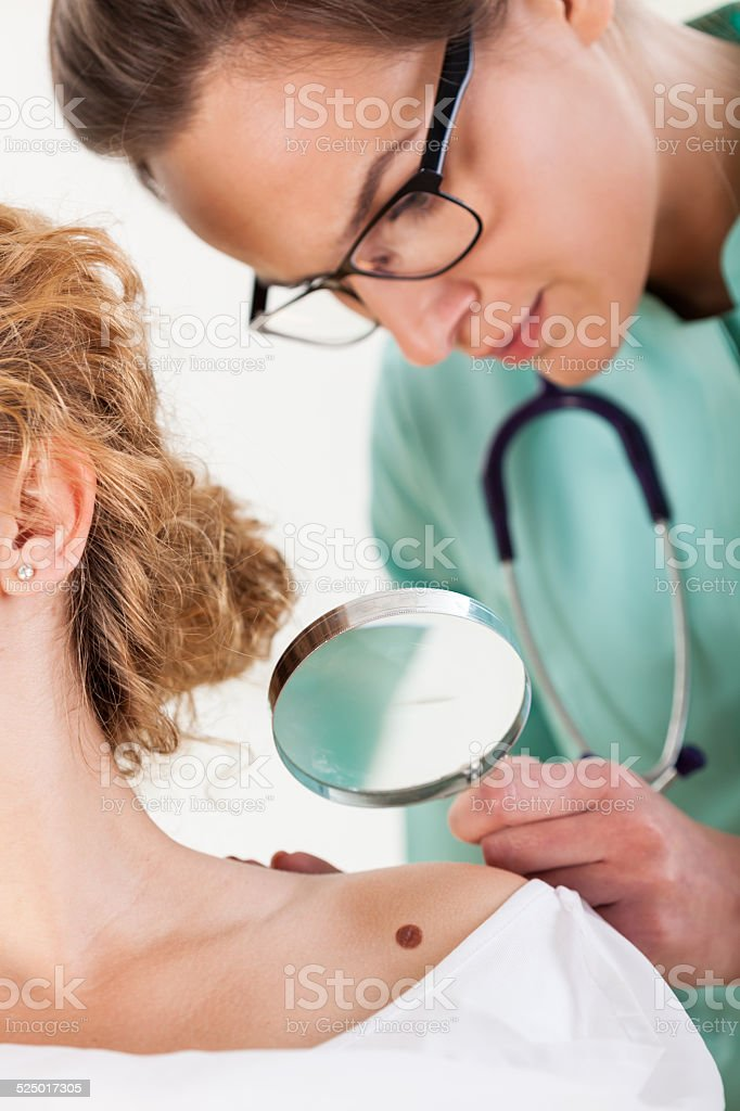 Dermatologist examining a mole stock photo