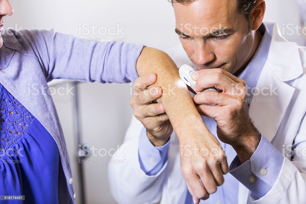 Dermatologist examining patient for skin cancer stock photo