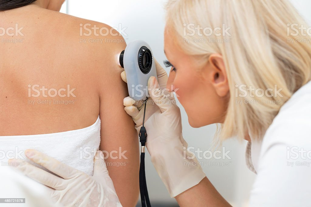 Dermatologist examining patient skin stock photo