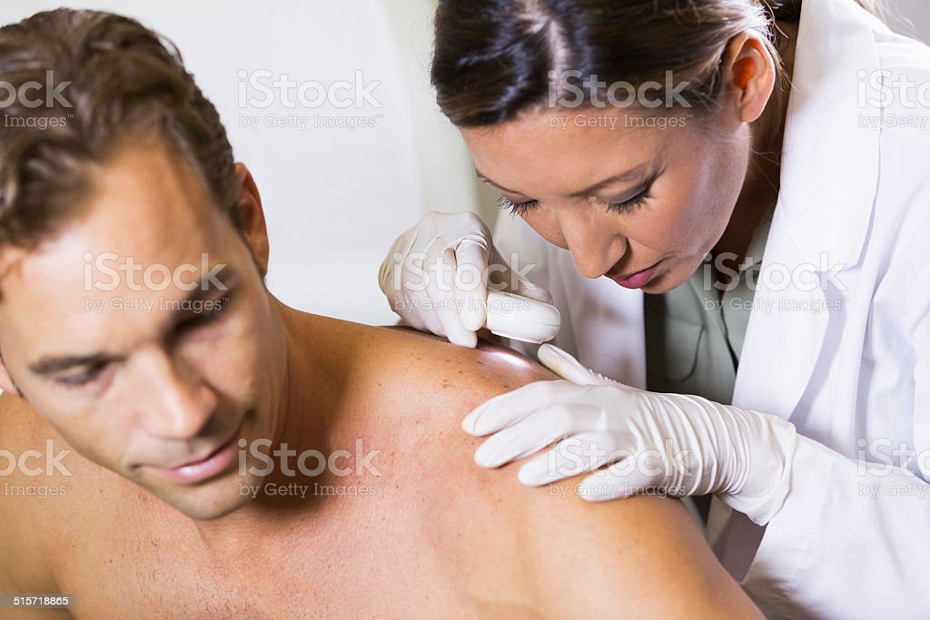 Dermatologist examining patient's skin for signs of cancer stock photo