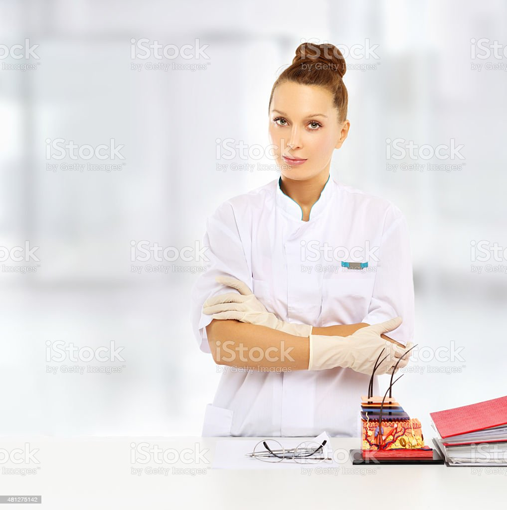Dermatologist  standing by her desk stock photo