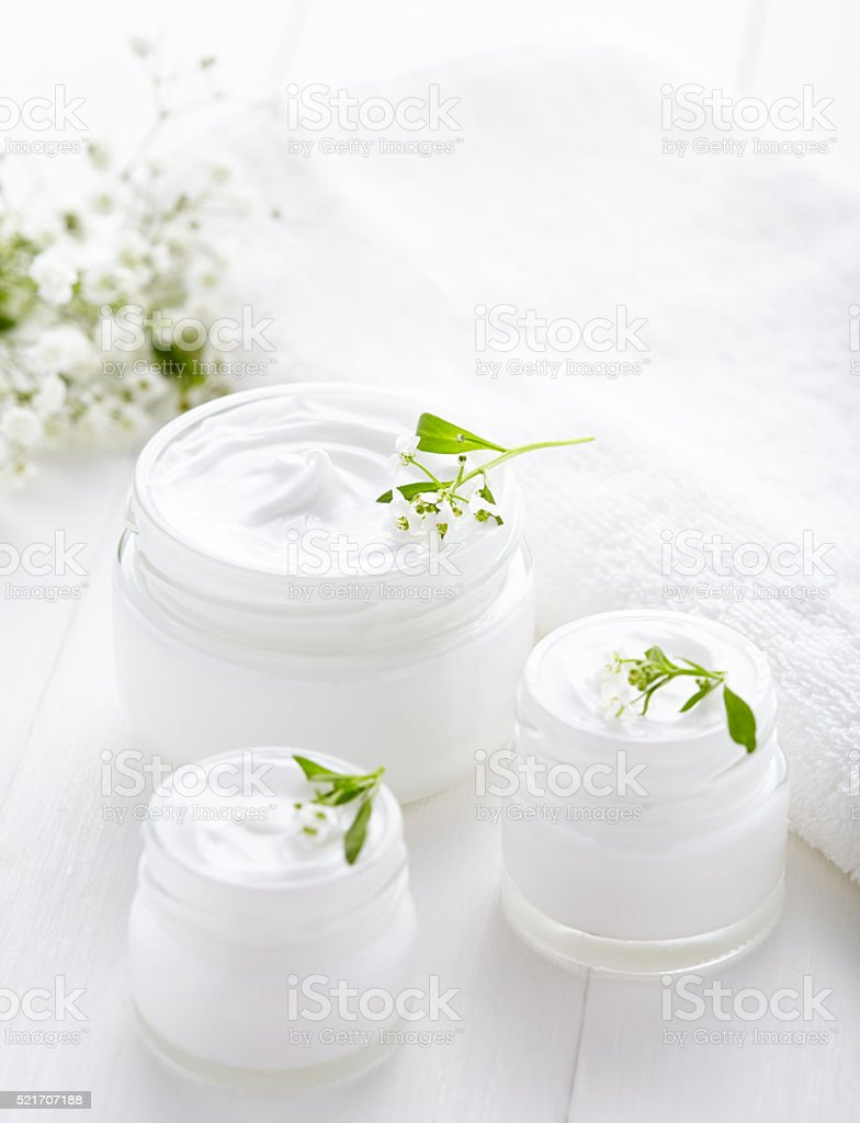 Dermatology herbal cosmetic cream with flowers hygienic skincare product stock photo