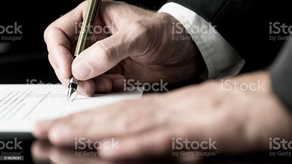 Desaturated image of signing a contract stock photo