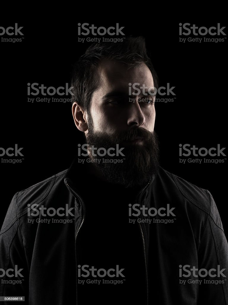 Desaturated serious bearded hipster looking away. stock photo