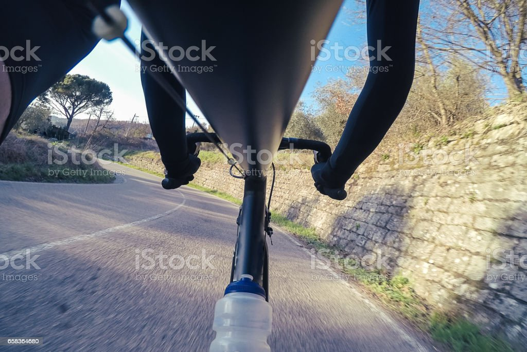 Descending on a mountain road on bicycle. POV. stock photo