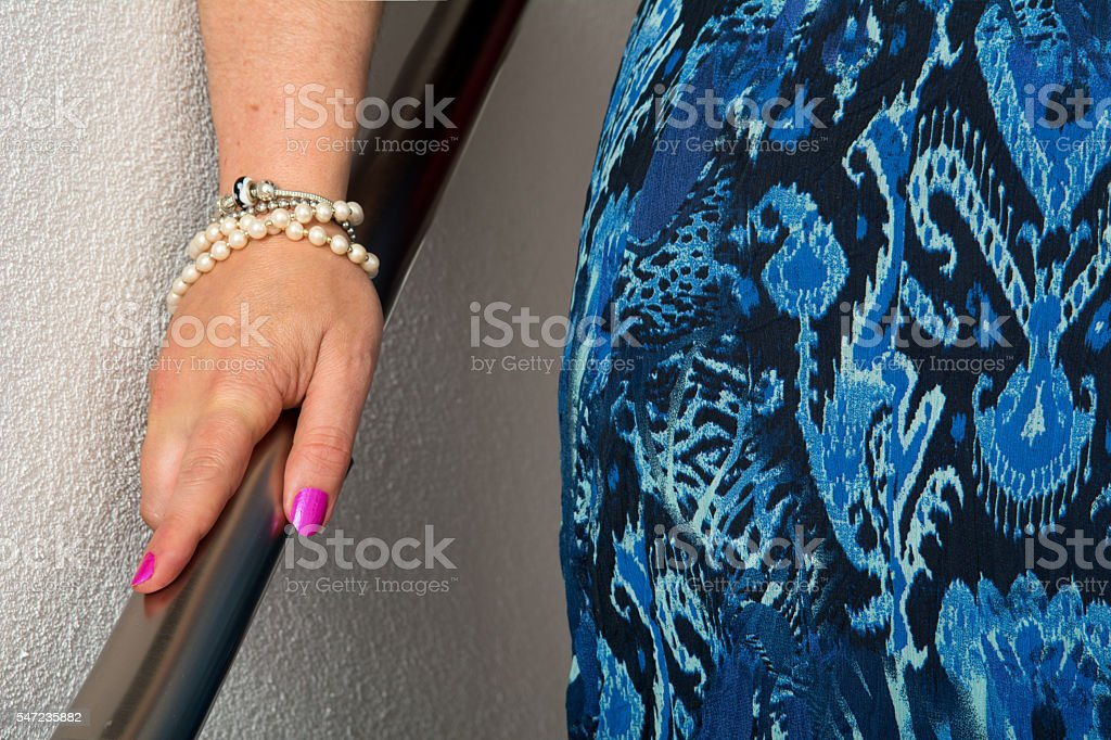 descending woman holding on to handrail going down the stairs stock photo
