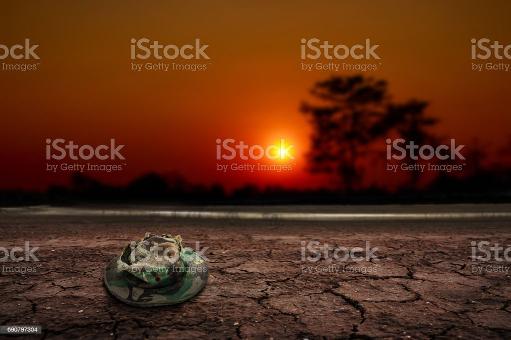 Desert ground sunset, Old soldier hat stock photo
