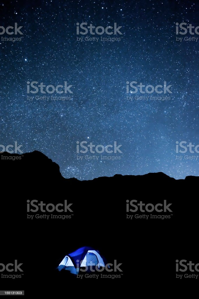 Desert night sky with camping tent and silhouetted cliffs stock photo