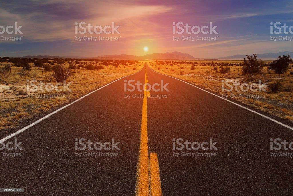 Desert Road and Sunset on Horizon stock photo