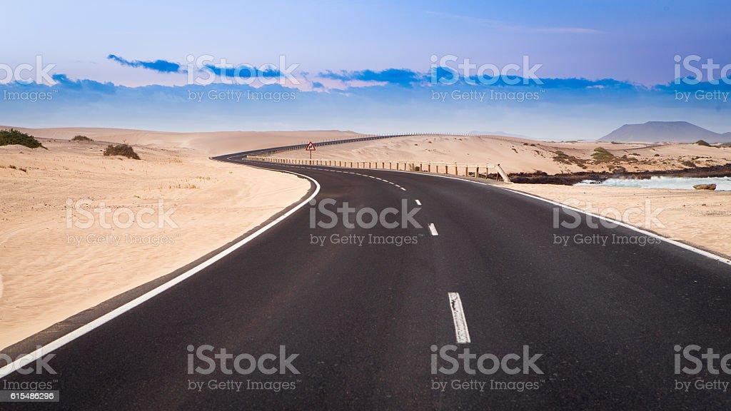 desert road winds through the dunes stock photo