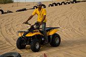 Desert safari camp staff riding an ATV (All Terrain Vehicle)