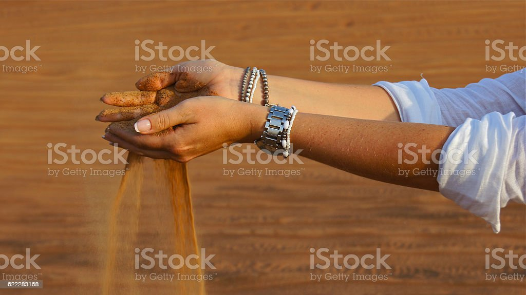 Desert sand in hands stock photo