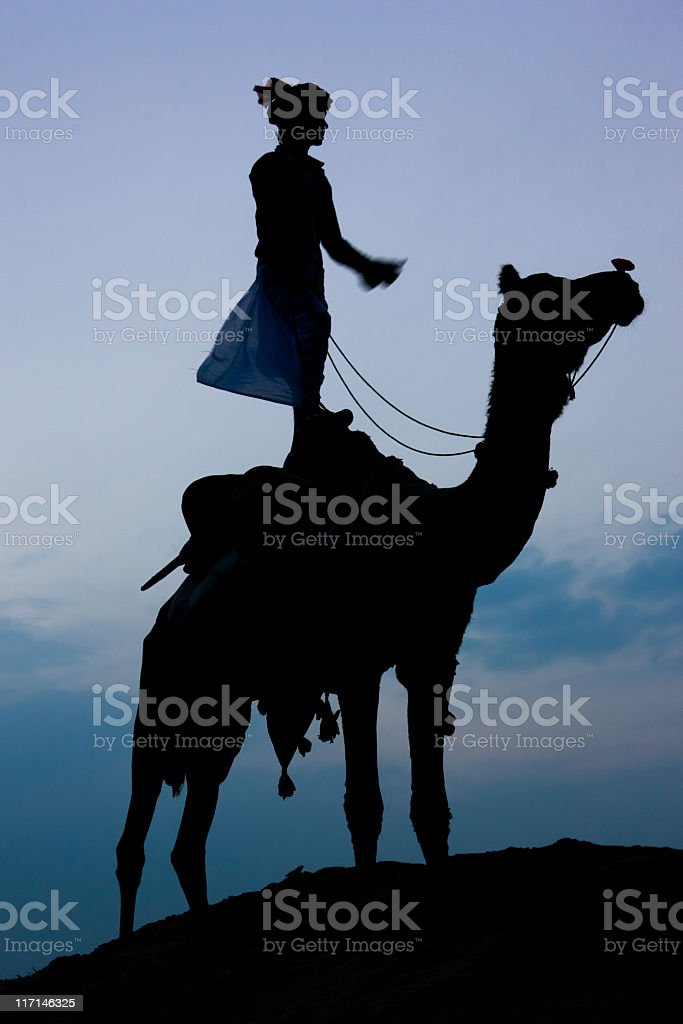 Desert Sunset Silhouette, Indian Boy standing on Camel stock photo