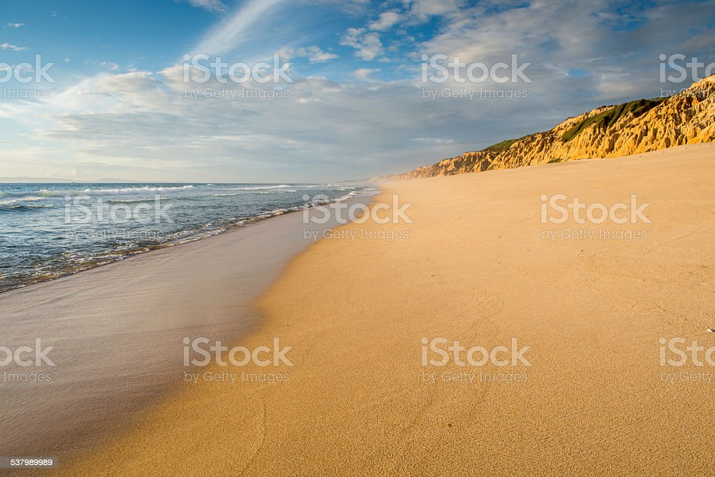 Deserted beach without people facing cliff stock photo