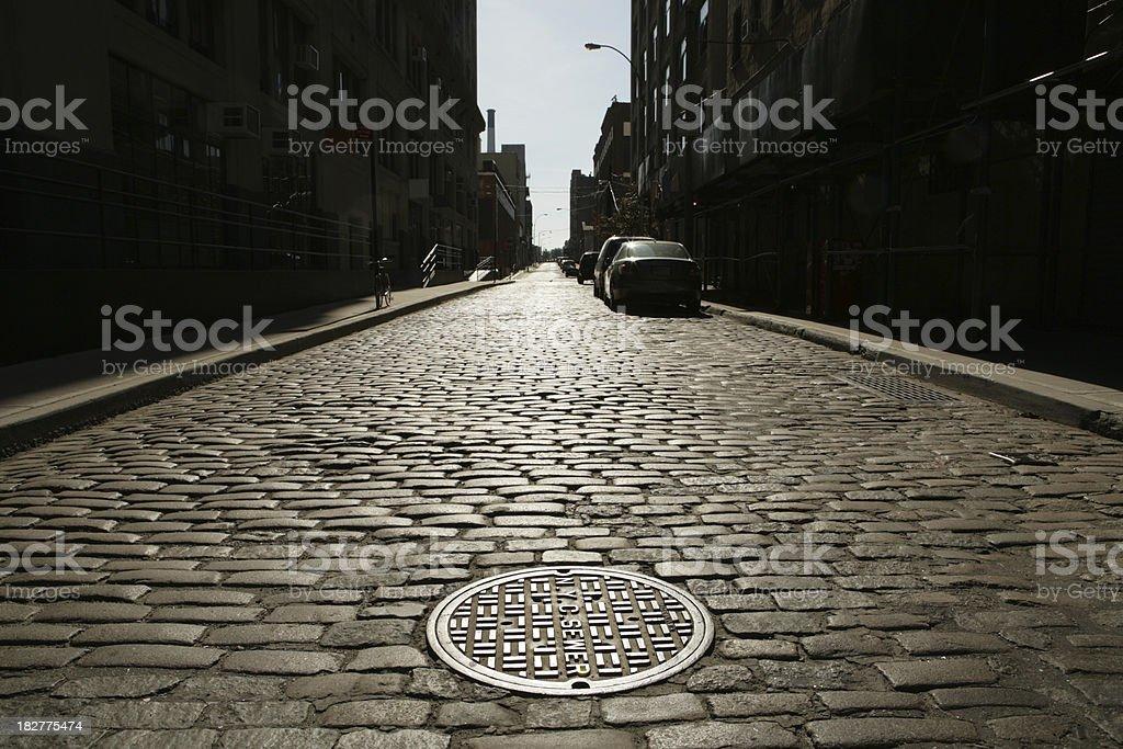 Deserted Brooklyn DUMBO Cobblestone Backstreet Sunrise Drain Cover NYC Sewer royalty-free stock photo
