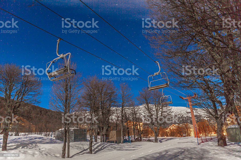 Deserted chair lift at night stock photo