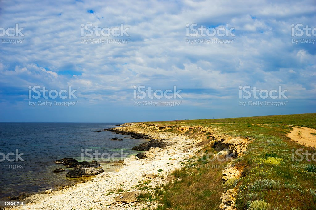 Deserted coast of the black sea with picturesque clouds. stock photo