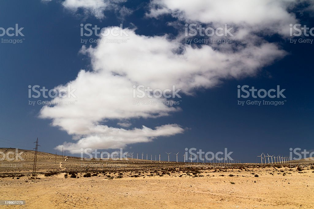 Desertic field with blue sky and wind turbines stock photo