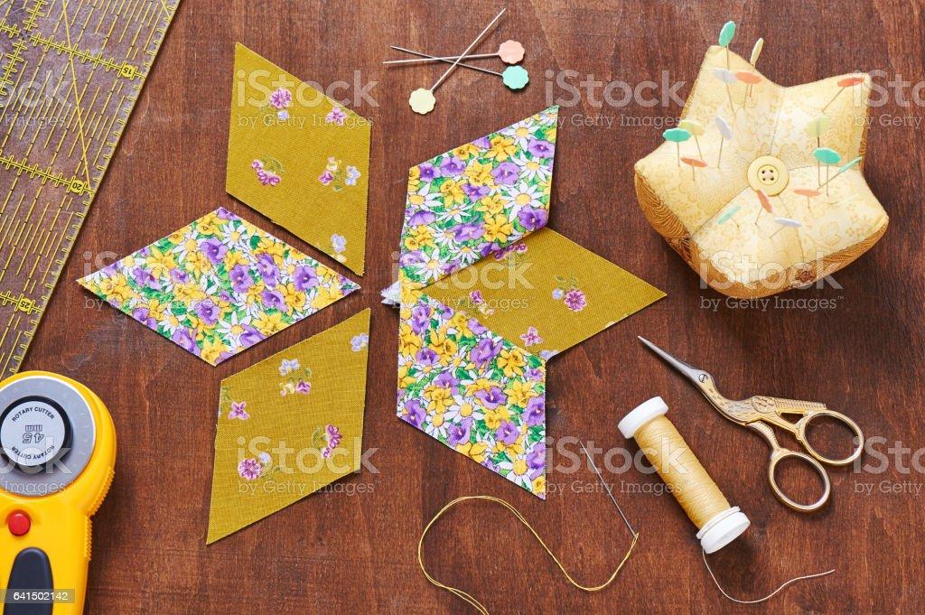 Design of  element quilt in progress, prepared cut pieces around accessories, top view stock photo