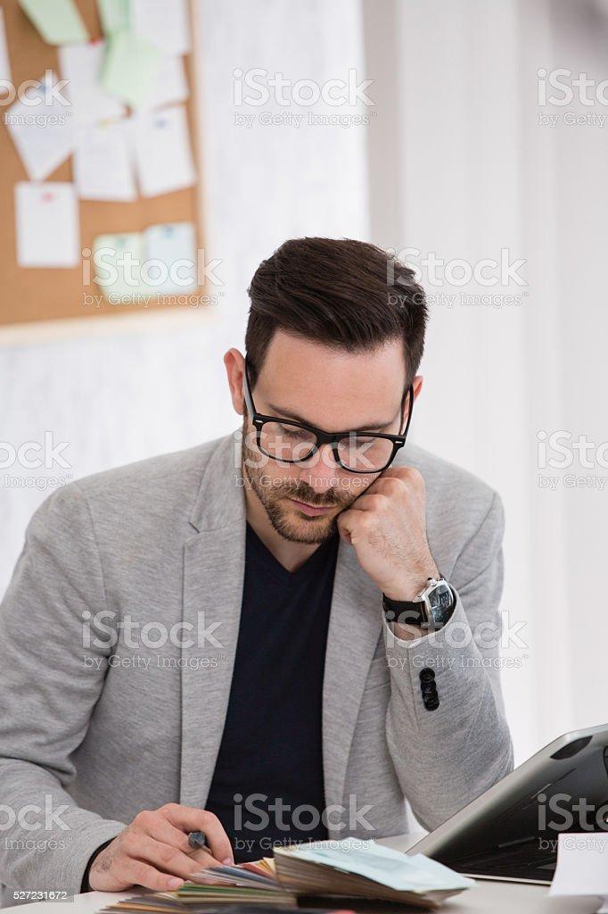 Designer choosing fabric samples at office stock photo